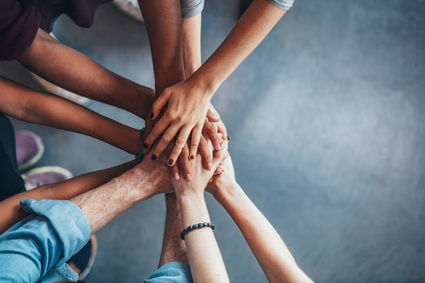 Junge Leute legen im Halbkreis ihre Hände aufeinander. Ausdruck von Einheitsgefühl und Teamwork.